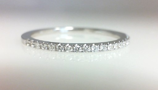 Diamond Wedding Band - Ladies 14 karat white gold high polished diamond wedding band.  This band features 18 prong set round brilliant cut diamonds.  The diamonds are H-I color, SI2 clarity and weigh 0.11 ct.  This band weighs 1.40 grams and is size 6.50.