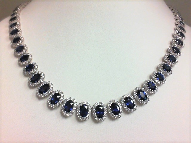Diamond Necklace - Ladies 18 karat white gold sapphire and diamond necklace.   This necklace features 62 prong set oval sapphires totaling 22.54 cts.  Surrounding the sapphires are prong set round diamonds.  The diamonds are G-H color, VS1-2 clarity and weigh 5.83 cts.  This necklace measure 16.00 inches in length and weighs 48.20 grams.